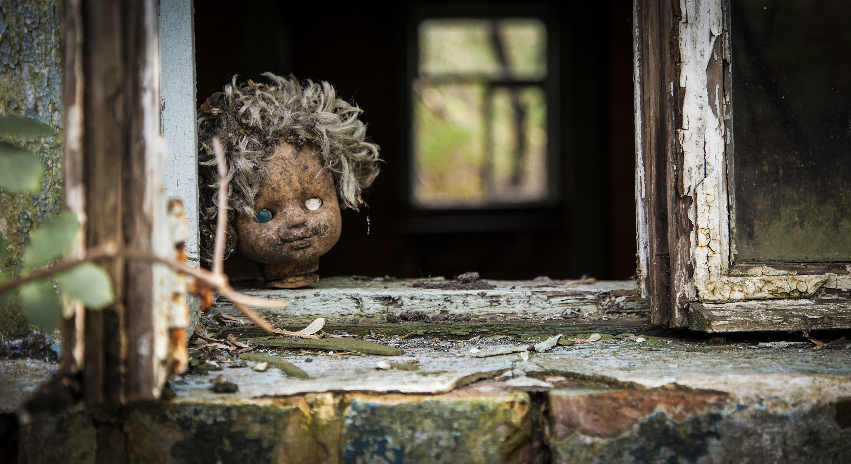 Old doll looks out a window in an abandoned house in Pripyat - Chernobyl nuclear power plant zone of alienation
